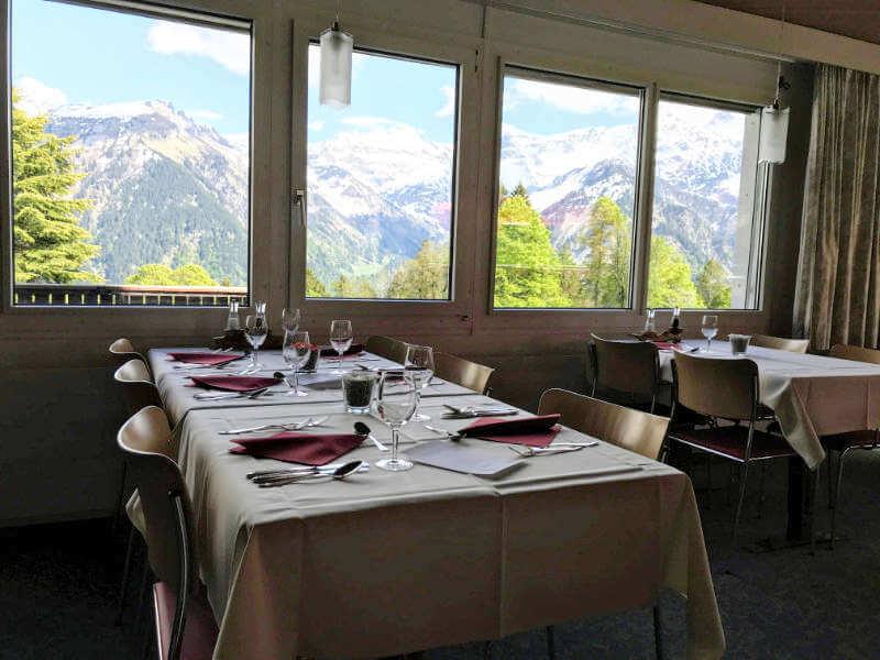 Aufgedeckte Tische im Restaurant vom Hotel Cristal mit Aussicht auf den Glarner Alpen